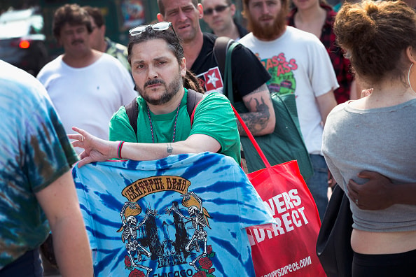 CHICAGO, IL - JULY 03:  Chato Arreguin sells t-shirts to Grateful Dead heading to a show at Soldier Field on July 3, 2015 in Chicago, Illinois. The show is one of three scheduled to be held in Chicago this weekend to mark the end of the band's 50 years together.  (Photo by Scott Olson/Getty Images)